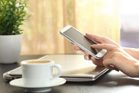 Close-up van een dame handen aanraken van een smart phone in een huis kamer over een tafel met een venster op de achtergrond