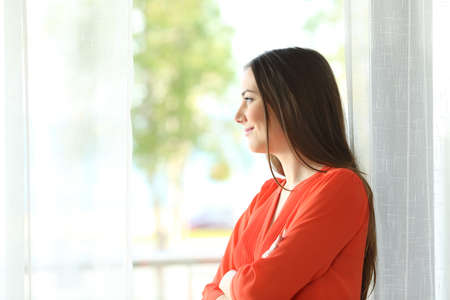 Side view portrait of a thoughtful attractive female looking the green background outside through a window of an hotel room or home Stock Photo