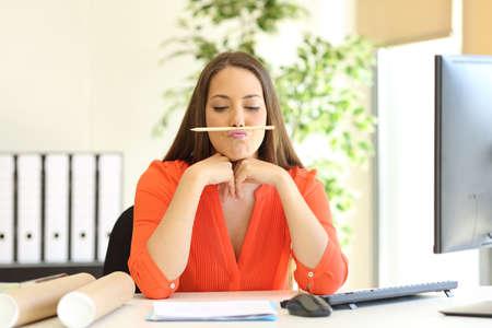 Nudí nebo neschopná podnikatelka hrát s tužkou na ploše v kanceláři Reklamní fotografie
