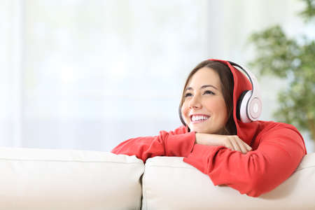 Dreamer teen girl listening music with headphones on a couch in the living room at home and looking above with copy space Stock fotó