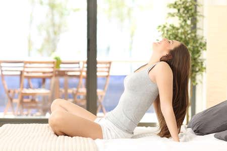 mujer meditando: Vista lateral de una mujer de la respiración y sentado en una cama en una habitación de hotel o casa con una ventana en el fondo