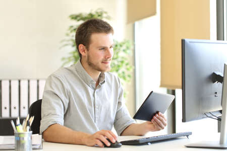 Negocios que trabaja con un equipo Tablet PC de escritorio y en la línea en la oficina