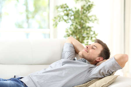 quiet adult: Relaxed man resting lying on a couch with the hands on the head at home