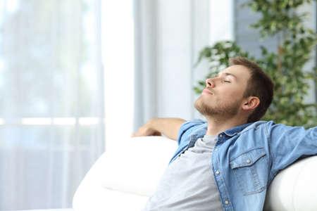 집에서 소파에 앉아 쉬고 캐주얼 피곤 된 남자의 초상화