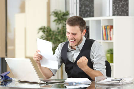 사무실에서 바탕 화면에 좋은 소식을 읽는 흥분된 사업가