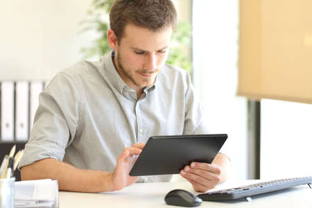 Entrepreneur working on line with a tablet sitting in a desk at office