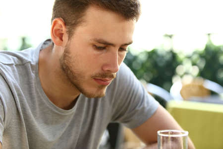 혼자 앉아서 레스토랑 테라스에서 밖에 마시는 매우 슬픈 한 남자의 초상