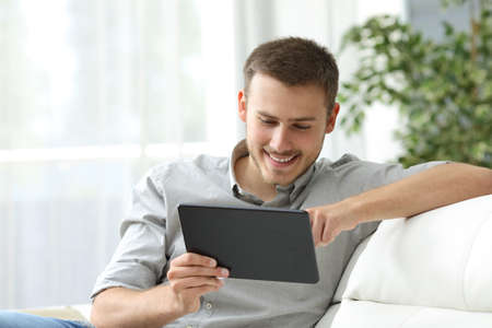 Happy man browsing in a tablet sitting on a couch at home Stock Photo