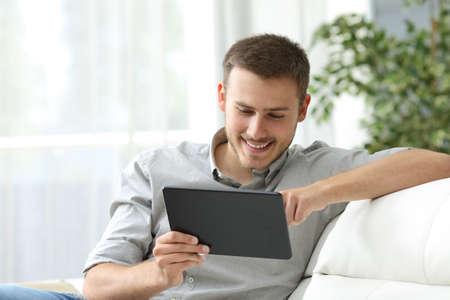 Heureux l'homme navigation dans un comprimé assis sur un canapé à la maison Banque d'images