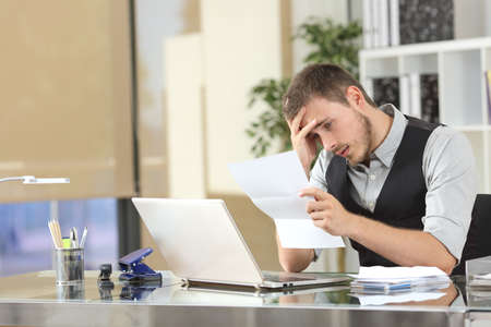 Uomo d'affari triste lettura cattive notizie in una lettera seduto in una scrivania in ufficio Archivio Fotografico - 65304714