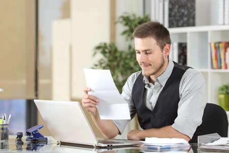 factura: Feliz hombre de negocios la lectura de una carta que se sienta en un escritorio en la oficina Foto de archivo