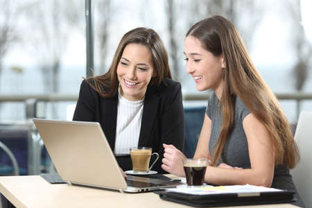 2 businesswomen working on line watching webs in a laptop in a bar with a window and and outdoors in the background