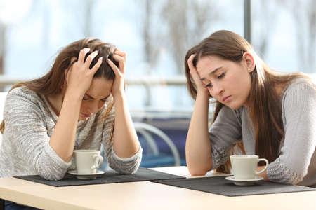 Twee droevige vrouwen bezorgd in een coffeeshop met een venster op de achtergrond