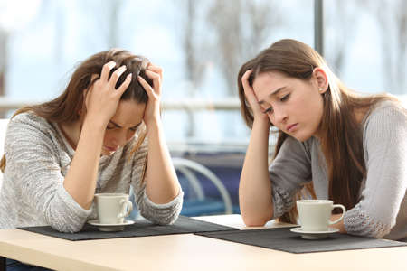 Two sad women worried in a coffee shop with a window in the background Stock Photo