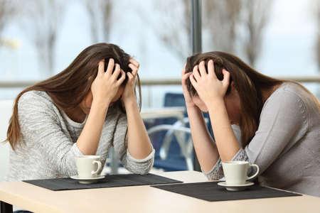 relaciones publicas: Dos muchachas tristes desesperado que grita con las manos sobre la cabeza en un bar con una ventana con un fondo de invierno