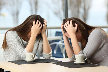 Two desperate sad girls crying with hands over head in a bar with a window with a winter background Stock Photo