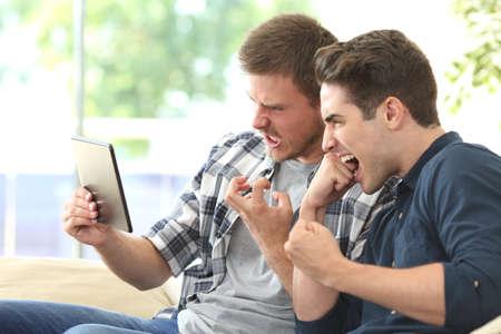 Dos amigos de ira en espera de contenido multimedia en línea en una tableta con una conexión lenta sentado en un sofá en la sala de estar en casa