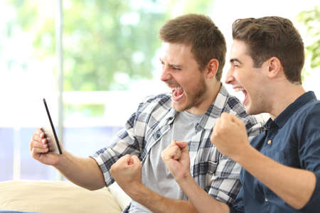 Two excited friends or roommates watching tv on line in a tablet sitting on a couch in the living room at home