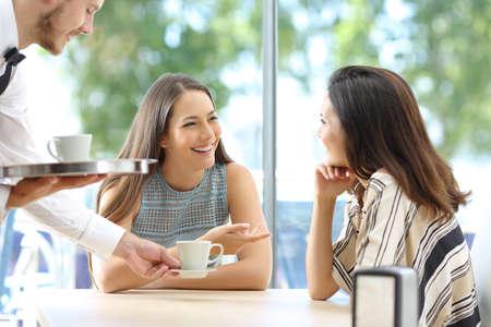 행복 한 친구 커피 잔을 제공하는 웨이터와 바의 테이블에 앉아 서로 찾고 이야기