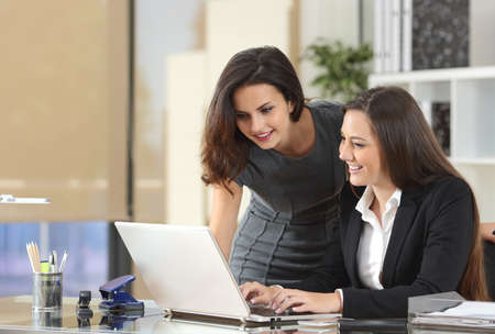Two happy businesswomen coworking with a laptop in a desktop at office Stok Fotoğraf