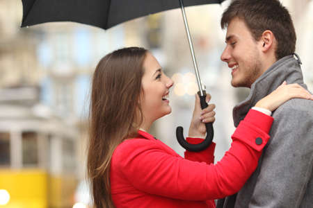 Side view of a couple encounter in the street under an umbrella in a rainy day Stock Photo