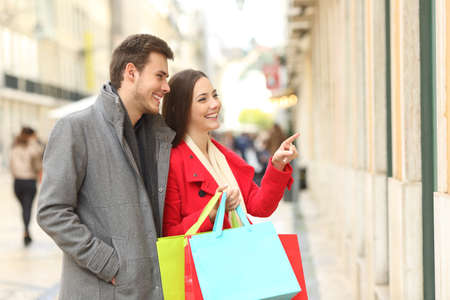 Couple of consumers watching storefronts and holding shopping bags in the street in winter