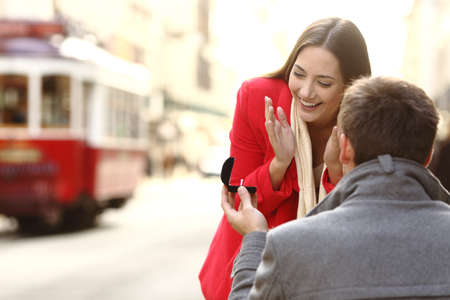 Vintage marriage proposal outdoors in the streets of portugal with a red tram in the background Archivio Fotografico