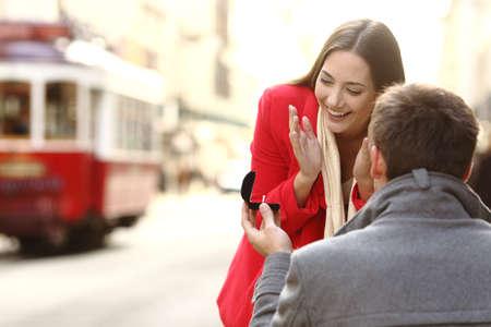 Uitstekend huwelijksvoorstel in openlucht in de straten van Portugal met een rode tram op de achtergrond