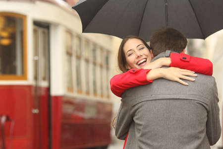 Encounter after a travel of a happy couple hugging in the street in a tram station in a rainy day under an umbrella