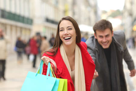 Front view of a casual couple of shoppers running in the street towards camera holding colorful shopping bags Stock Photo