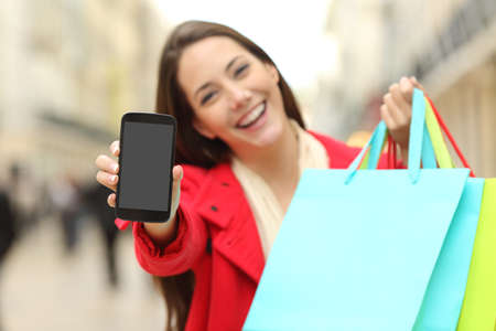 Front view of a shopper holding blank shopping bags showing to the camera a smart phone screen with an urban background