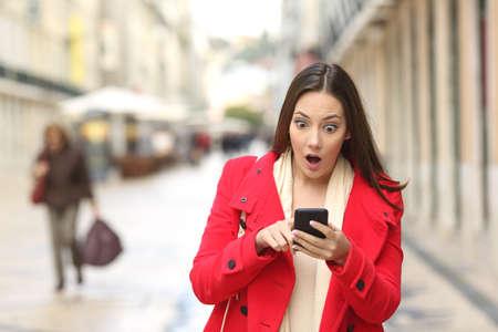 Vista frontal de una mujer sorprendente comprobar la moda teléfono inteligente en la calle y caminando hacia la cámara