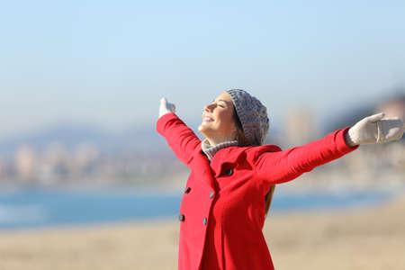 Gelukkige vrouw draagt een rode jas inademen van frisse lucht en verhoging van de armen op het strand in een zonnige dag van de winter
