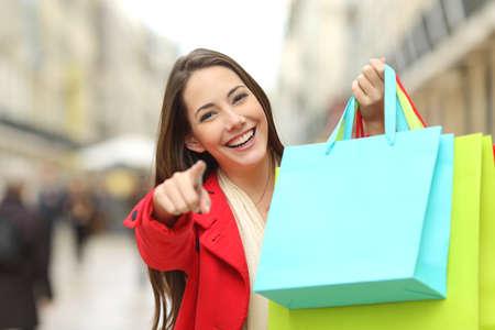 Gelukkige klant draagt rode jas met lege kleurrijke boodschappentassen en wijst u in de straat