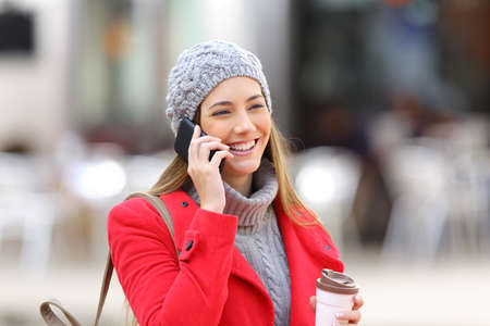 winter fashion: Happy woman calling on the mobile phone and holding a take away coffee in the street in winter Stock Photo