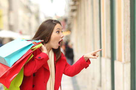 Amazed shopper opening mouth holding shopping bags watching special offers in stores and pointing in the street in winter