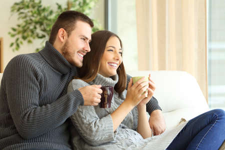 winter wedding: Affectionate couple wearing sweater holding hot coffee cups sitting on a sofa in the living room at home in winter
