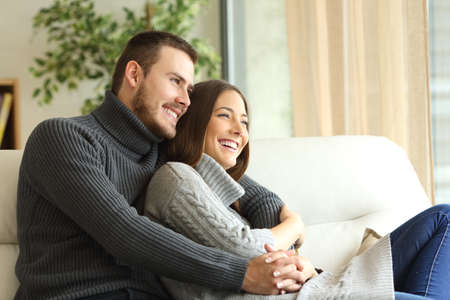 Affectionate couple wearing jersey resting and looking outdoors through a window sitting on a couch in the living room at home