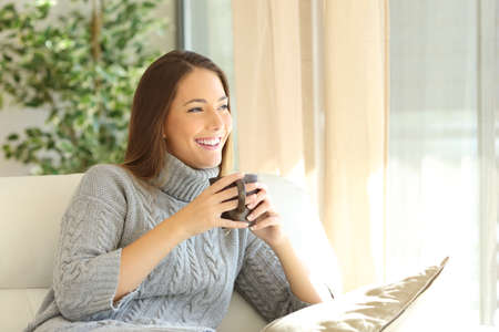 Pensive woman wearing a sweater holding a cup of coffee looking through a window sitting on a sofa at home in winter