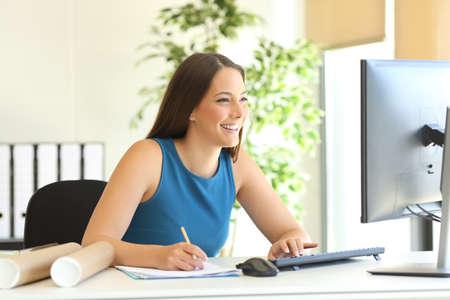 Gelukkig zakenvrouw werken op de lijn met een computer en het maken van aantekeningen op het kantoor van Stockfoto
