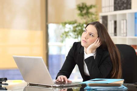 Bezorgd nadenkend zakenvrouw zijwaarts op zoek in een Desktop op kantoor
