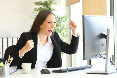 オフィスでデスクトップ コンピューターのモニターを見て腕を上げるスーツを着て興奮しているエグゼクティブ