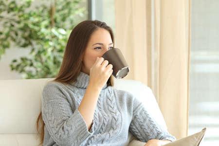Vrouw die sweater het drinken koffie draagt ??en door een vensterzitting op een laag thuis in de winter kijkt Stockfoto
