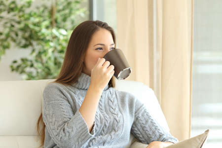 Woman wearing sweater drinking coffee and looking through a window sitting on a couch at home in winter Imagens