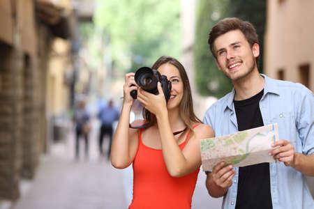 観光客の男性と女性のランドマークを古い町の通りにデジタル一眼レフ カメラで撮影のうれしそうなカップル 写真素材