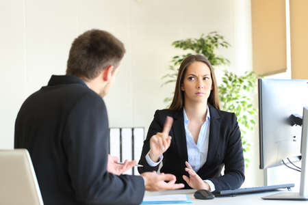 Boss denying something saying no with a finger gesture to an upset employee in her office