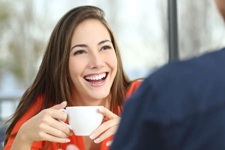 Portrait of a happy woman dating with perfect smile and white teeth in a snack bar interior with a window and outdoors in the background