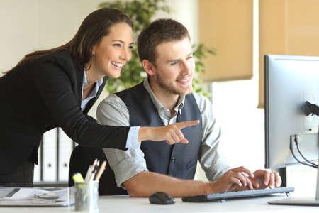 Compañeros de trabajo que trabajan en línea con un ordenador de sobremesa en un escritorio en la oficina con una ventana en el fondo Foto de archivo - 68707812