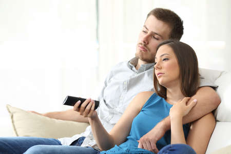 weary: Couple bored watching tv with a the hand holding the remote control sitting on a sofa at home Stock Photo