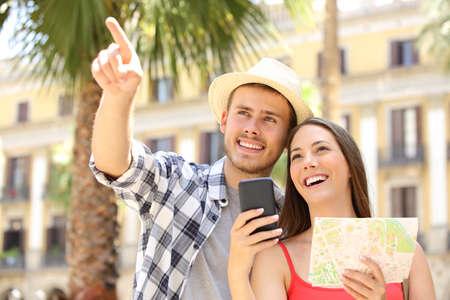 관광객의 관광객과 백그라운드에서 건물과 야자수가있는 거리의 랜드 마크를 가리키는 행복 한 커플